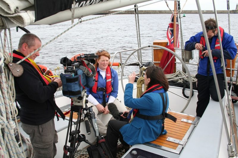 TV journalist and cameraman interview crew of James Cook from OYT North charity