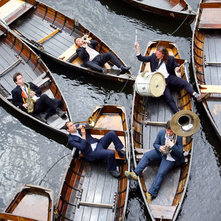 Musicians play a floating concert on rowing boats